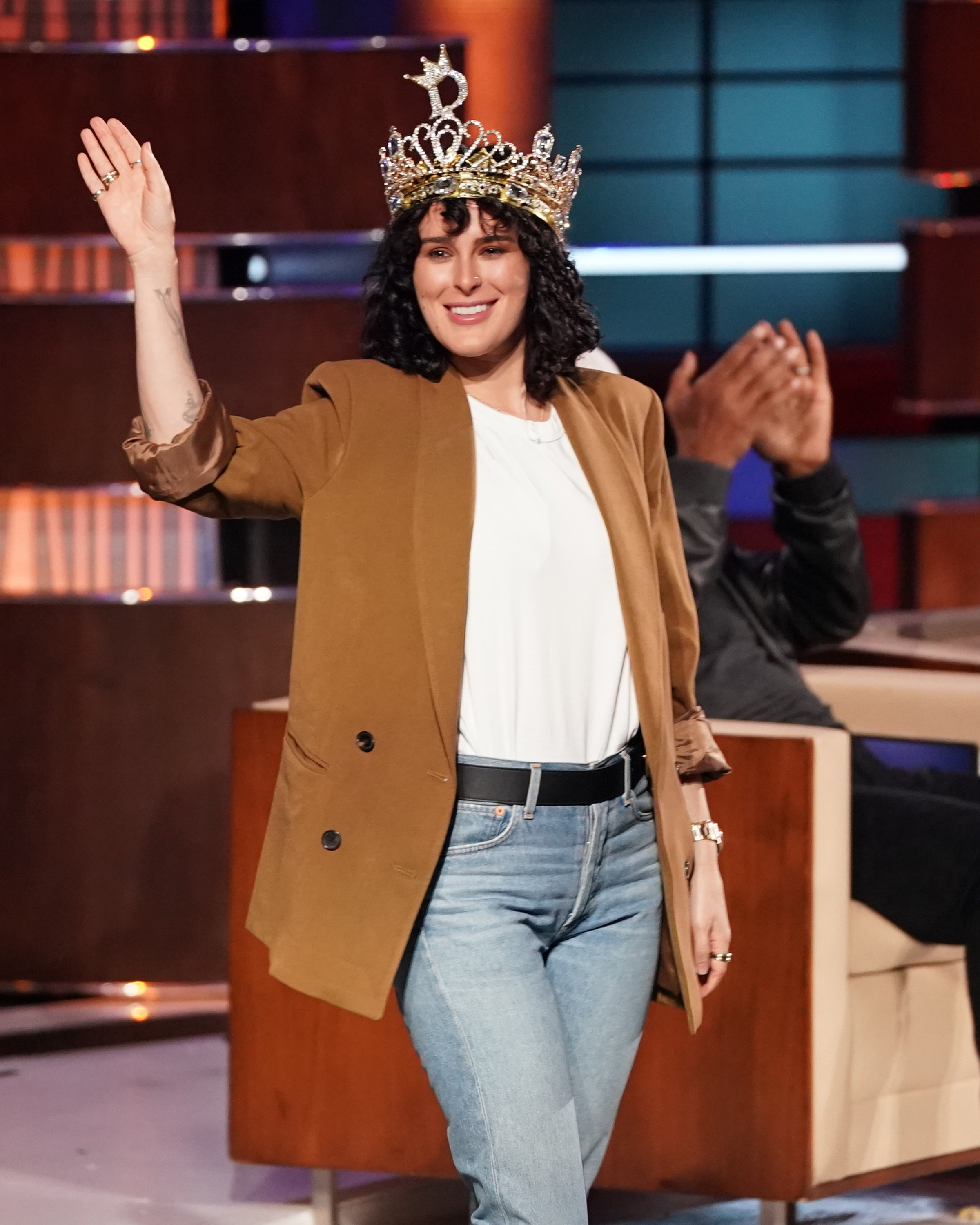 Rumer wearing a crown, tan jacket, and jeans and waving