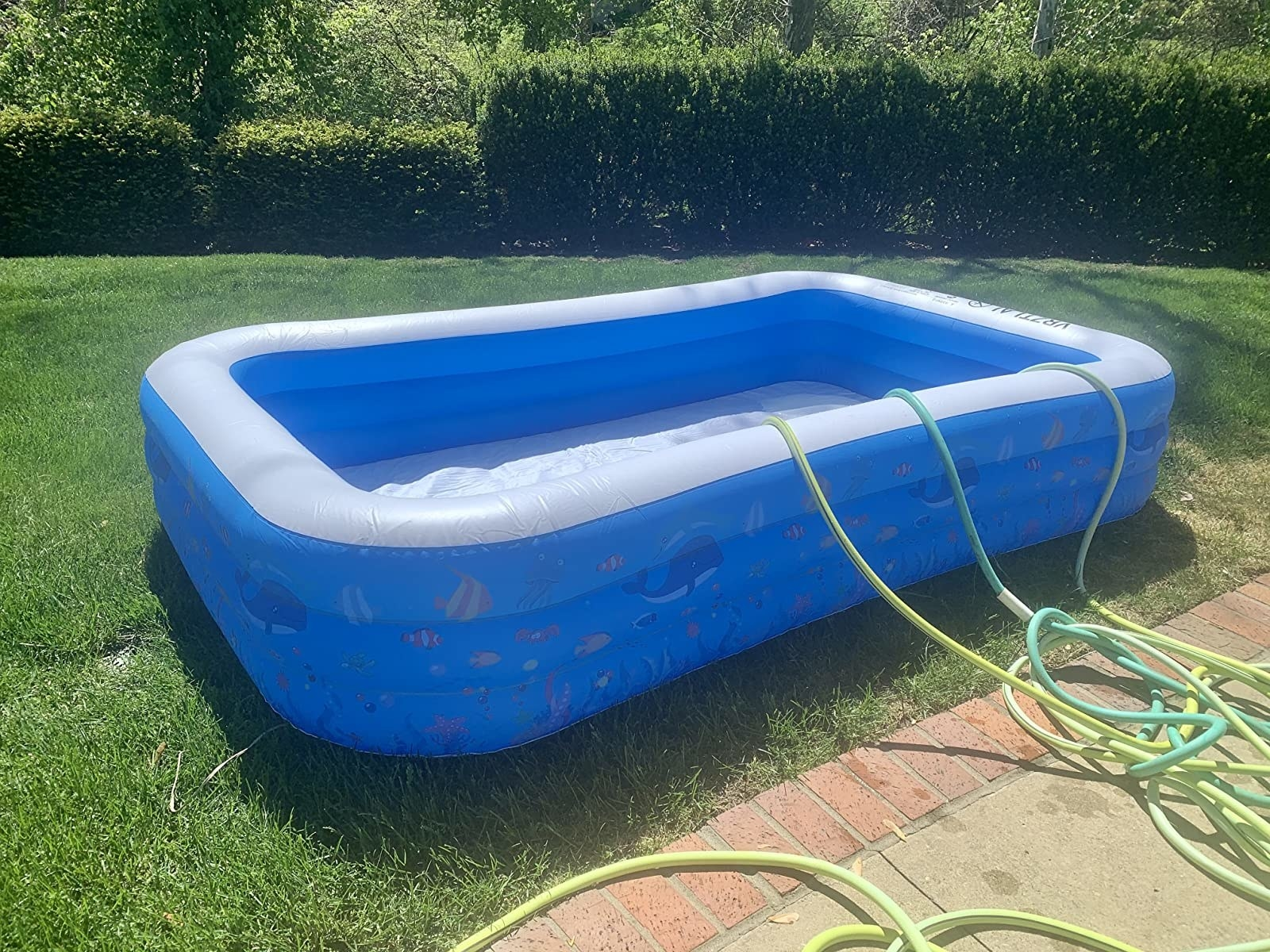 reviewer image of an inflated full-sized pool being filled with water from three hoses
