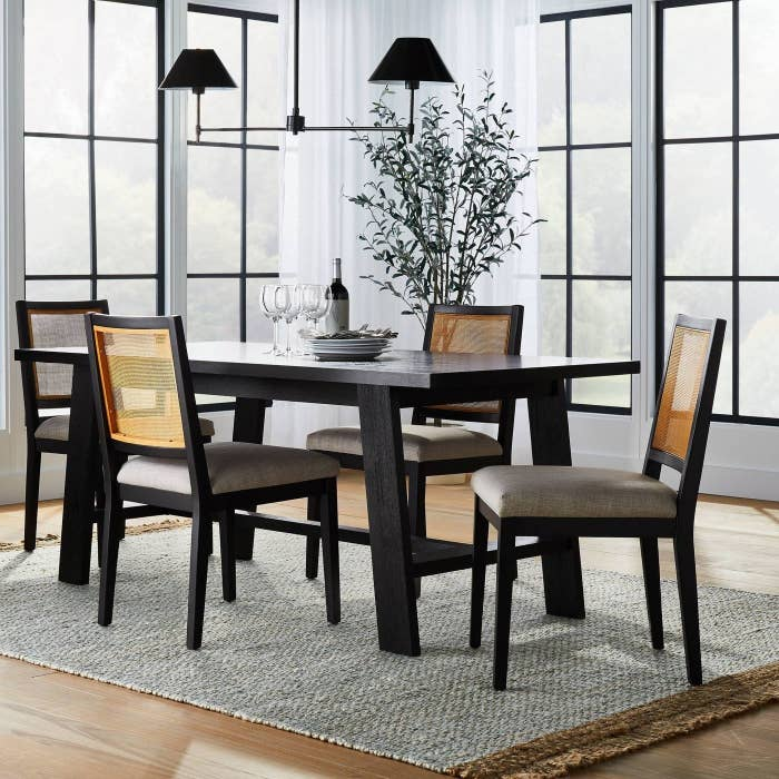 a set of four black and cane chairs around a black dining room table