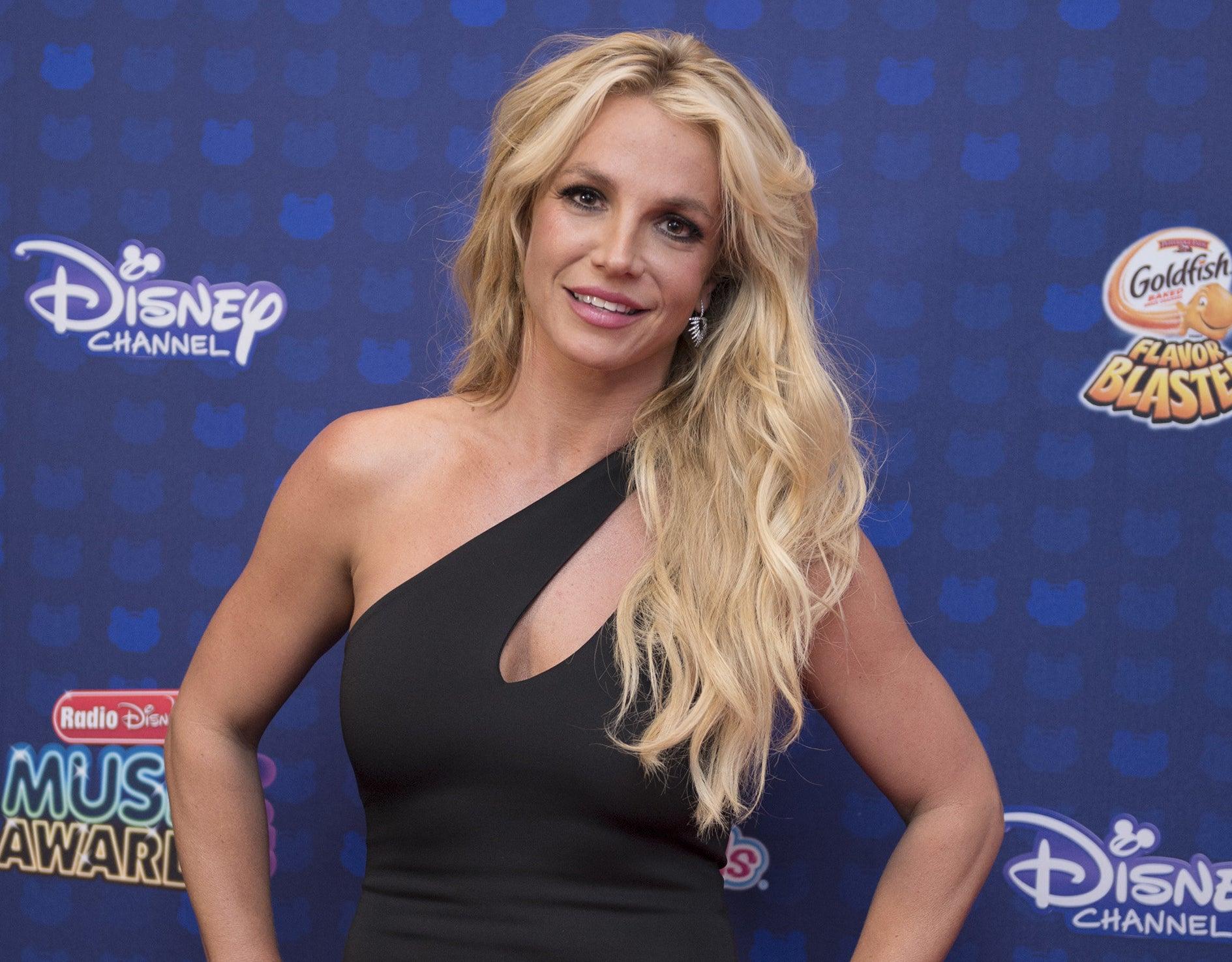 Britney puts both her hands on her hips in a black one-shoulder dress