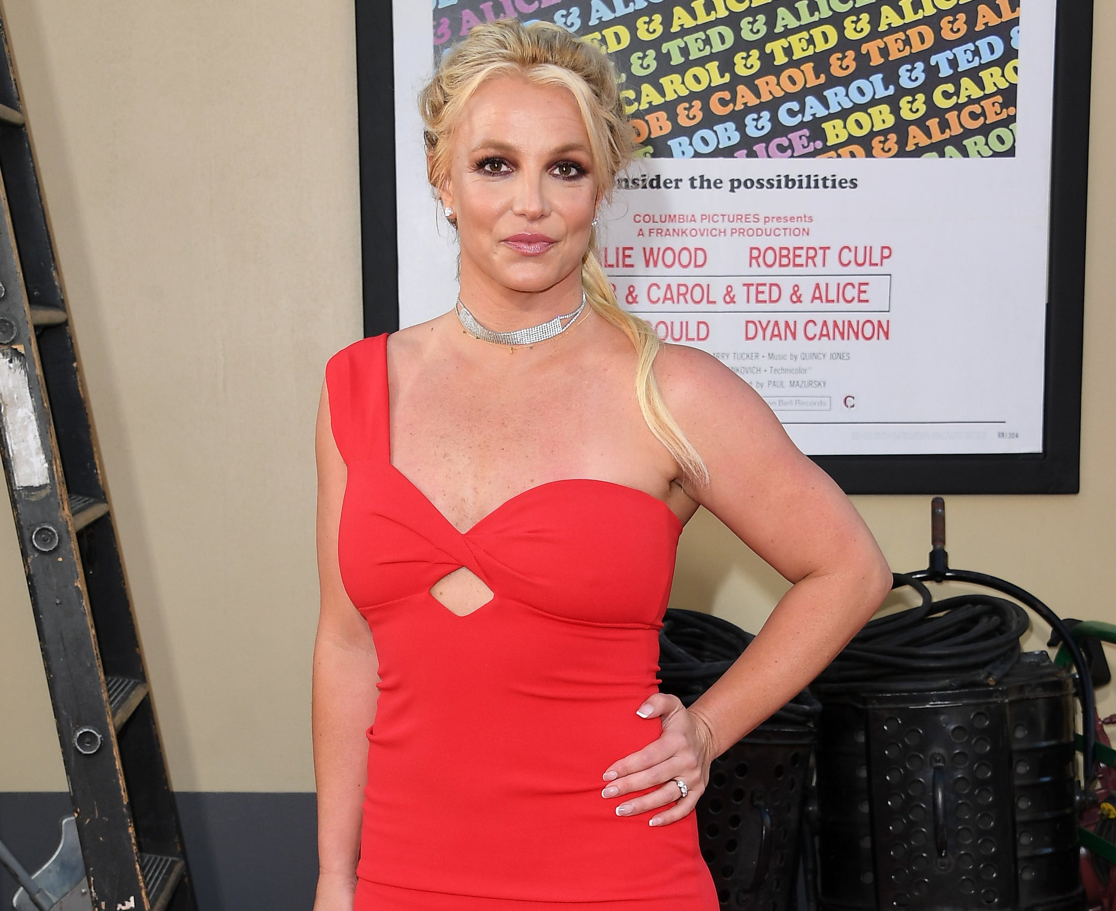 Britney puts her hands on her hip in a red one-shoulder dress