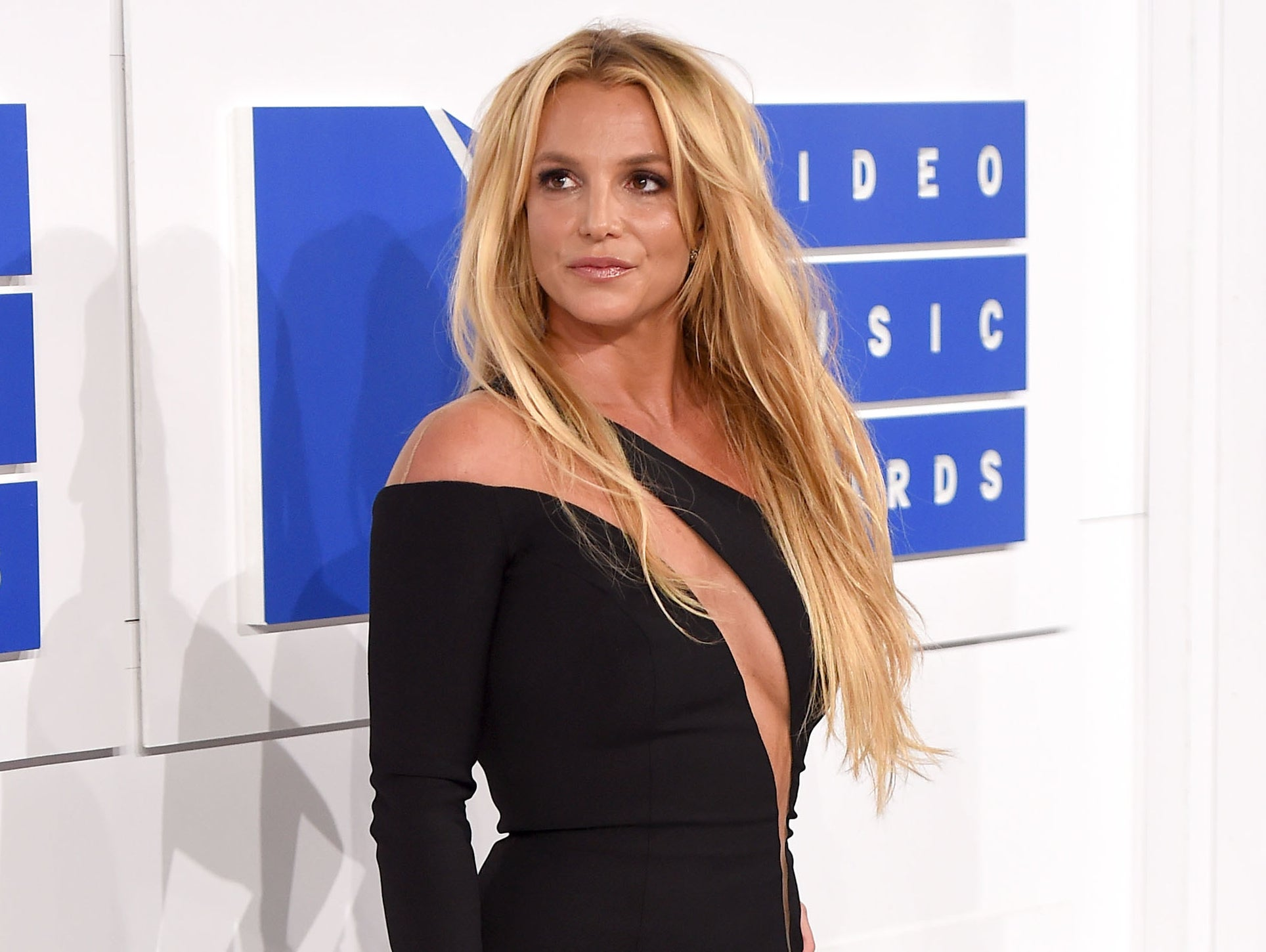 Britney looks into the distance while posing on a red carpet