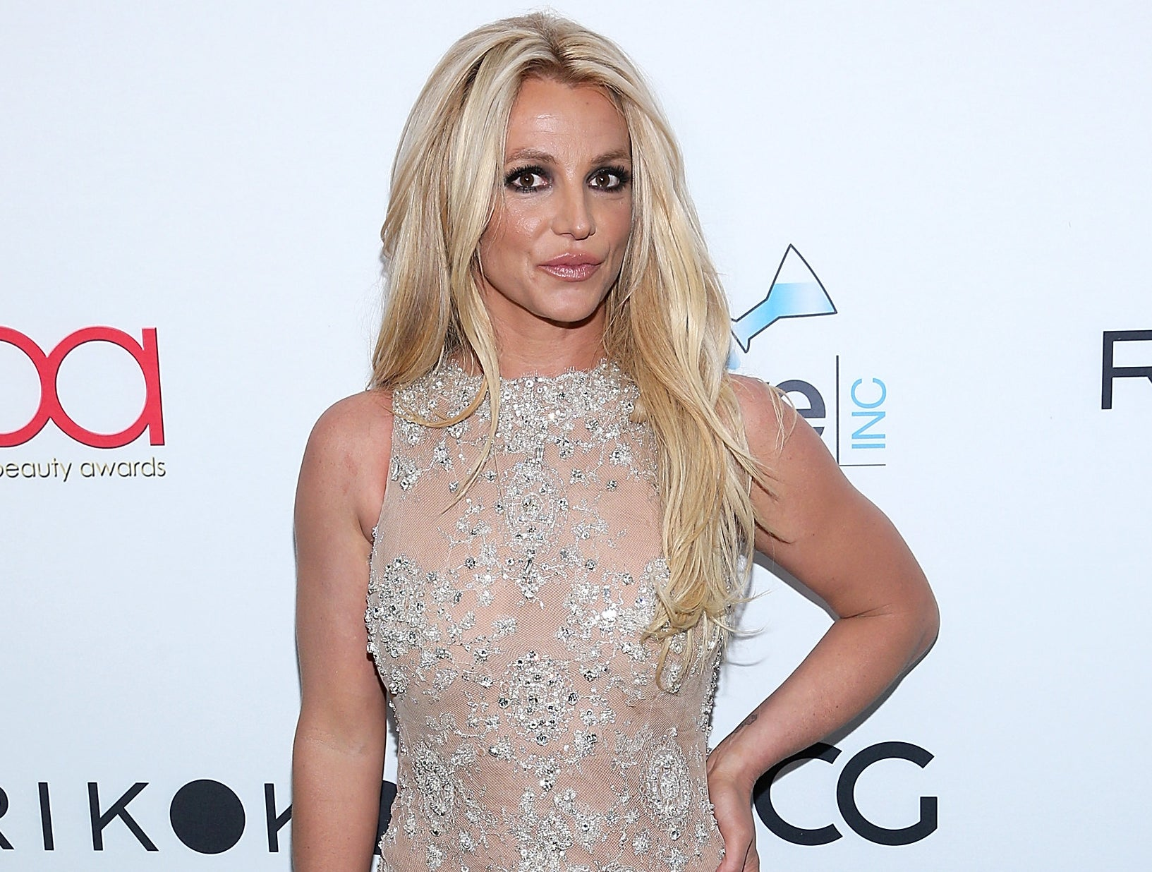 Britney wears a sheer sleeveless dress with silver jeweled detailing