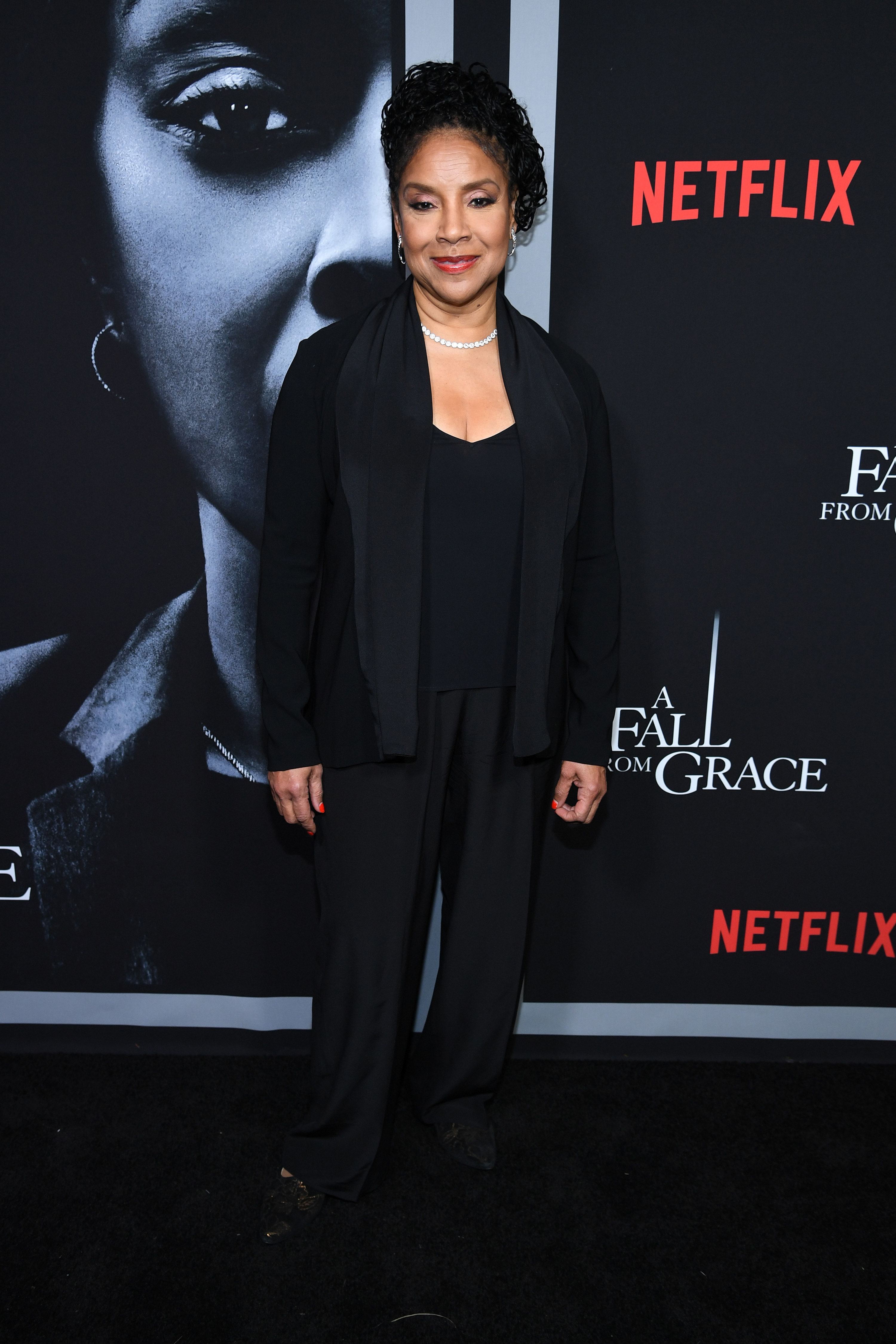 Rashad wears a blouse, blazer, and pants at a red carpet event in 2020