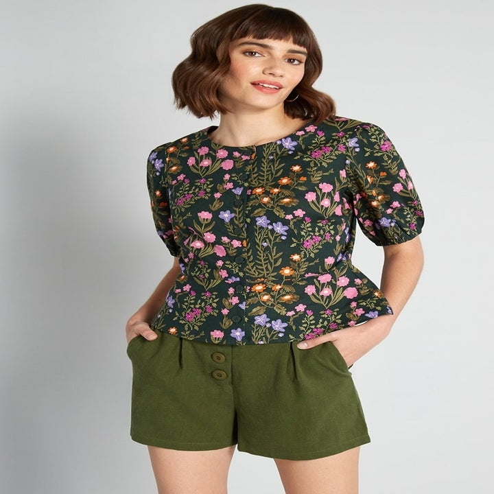 model wearing peplum navy blue floral blouse