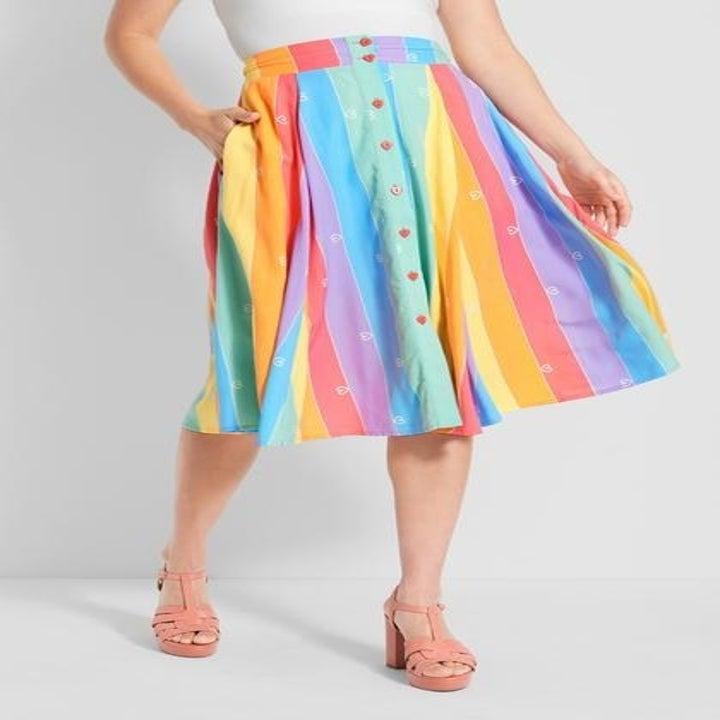 model wearing knee-length buttondown rainbow stripe skirt