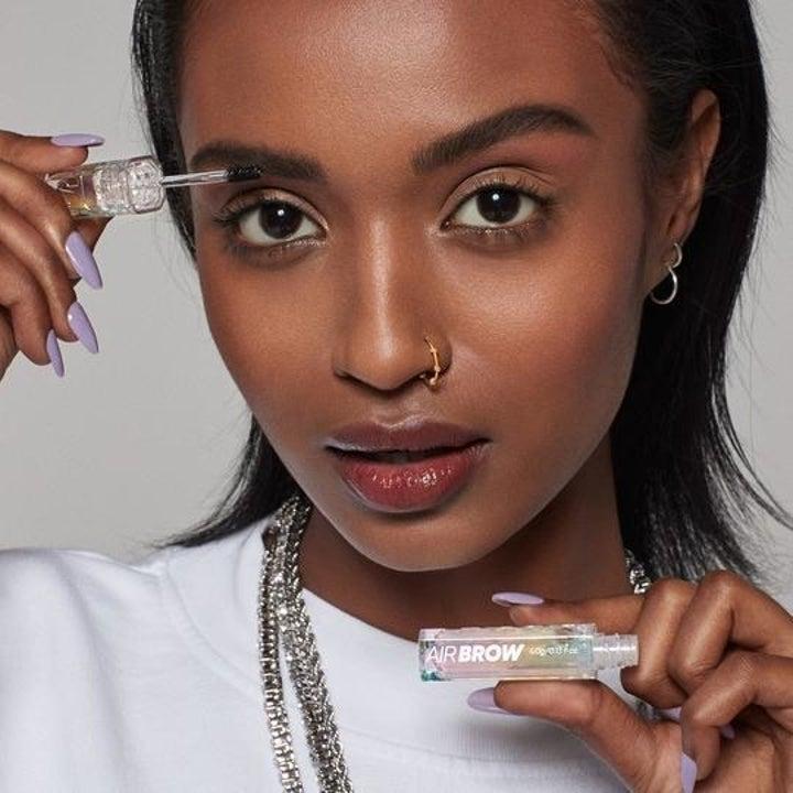 model applying clear brow gel to their eyebrow