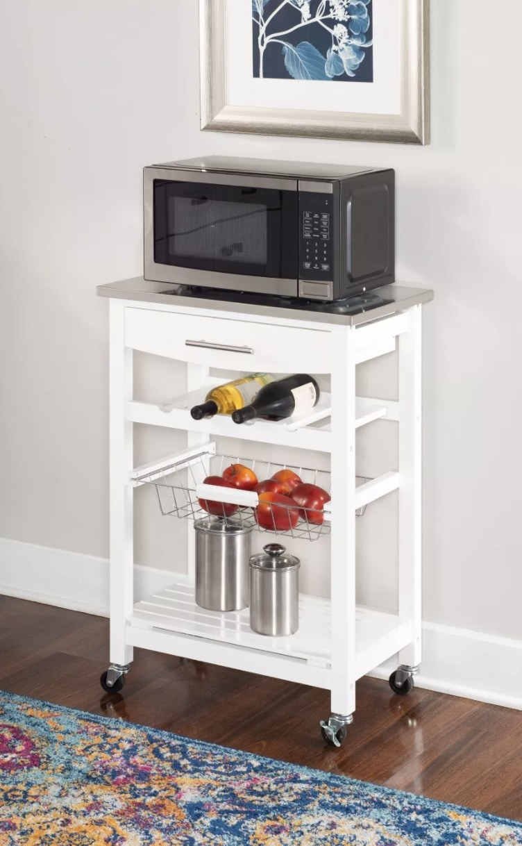 Kitchen cart holding microwave and other kitchen goods