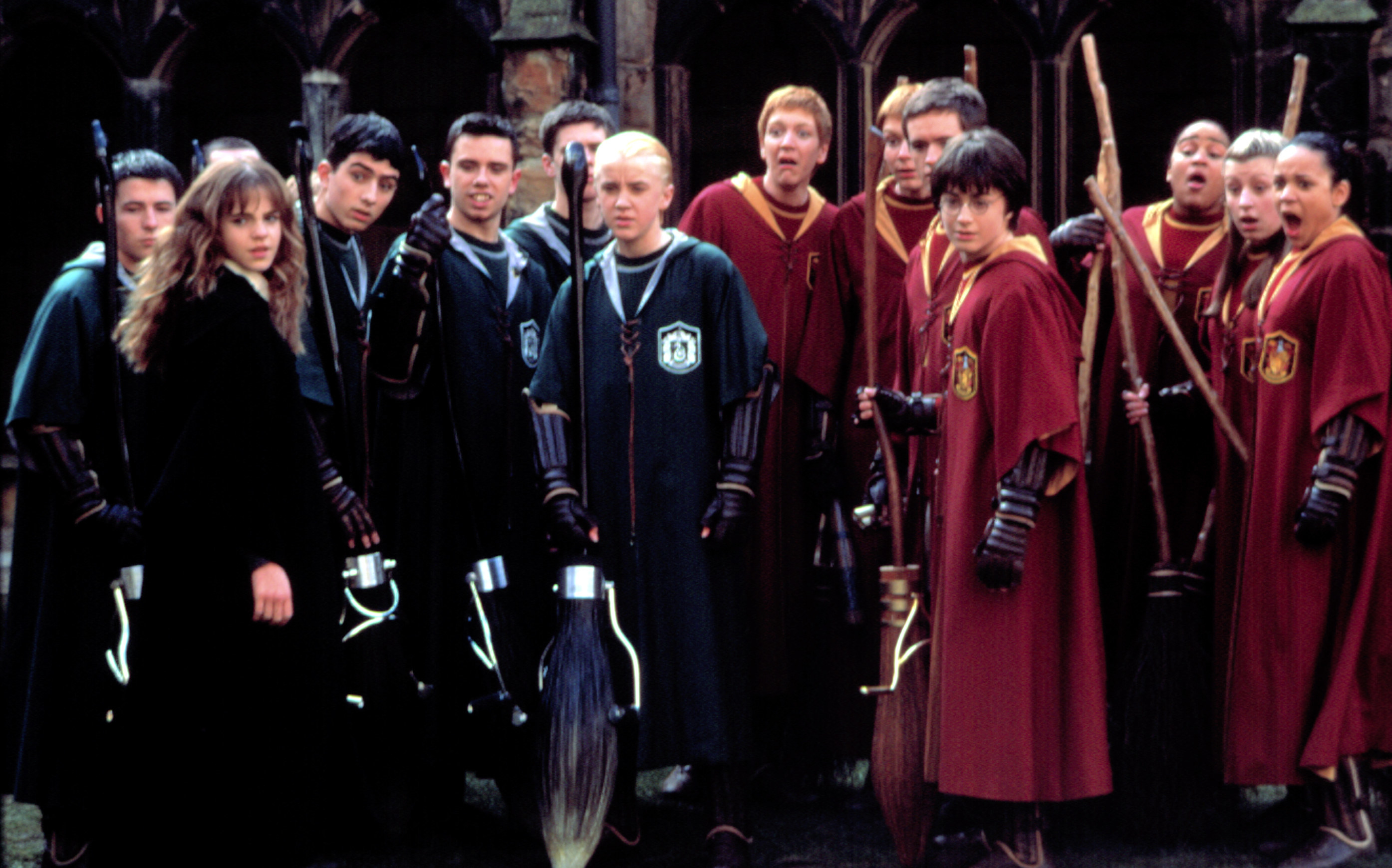 The cast of Harry Potter and the Chamber of Secrets brandishes their brooms