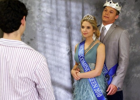 Hannah wears a homecoming queen sash and crown and is hugged from behind by her boyfriend on Pretty Little Liars