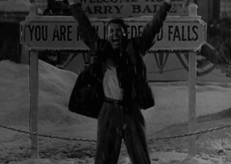 George Bailey cheers in front of the Bedford Falls sign in the snow in It's A Wonderful life