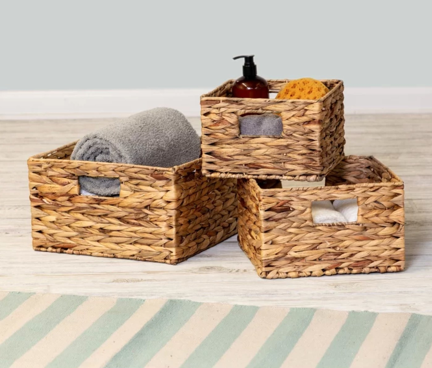 The set of wicker baskets holding toiletries and towels