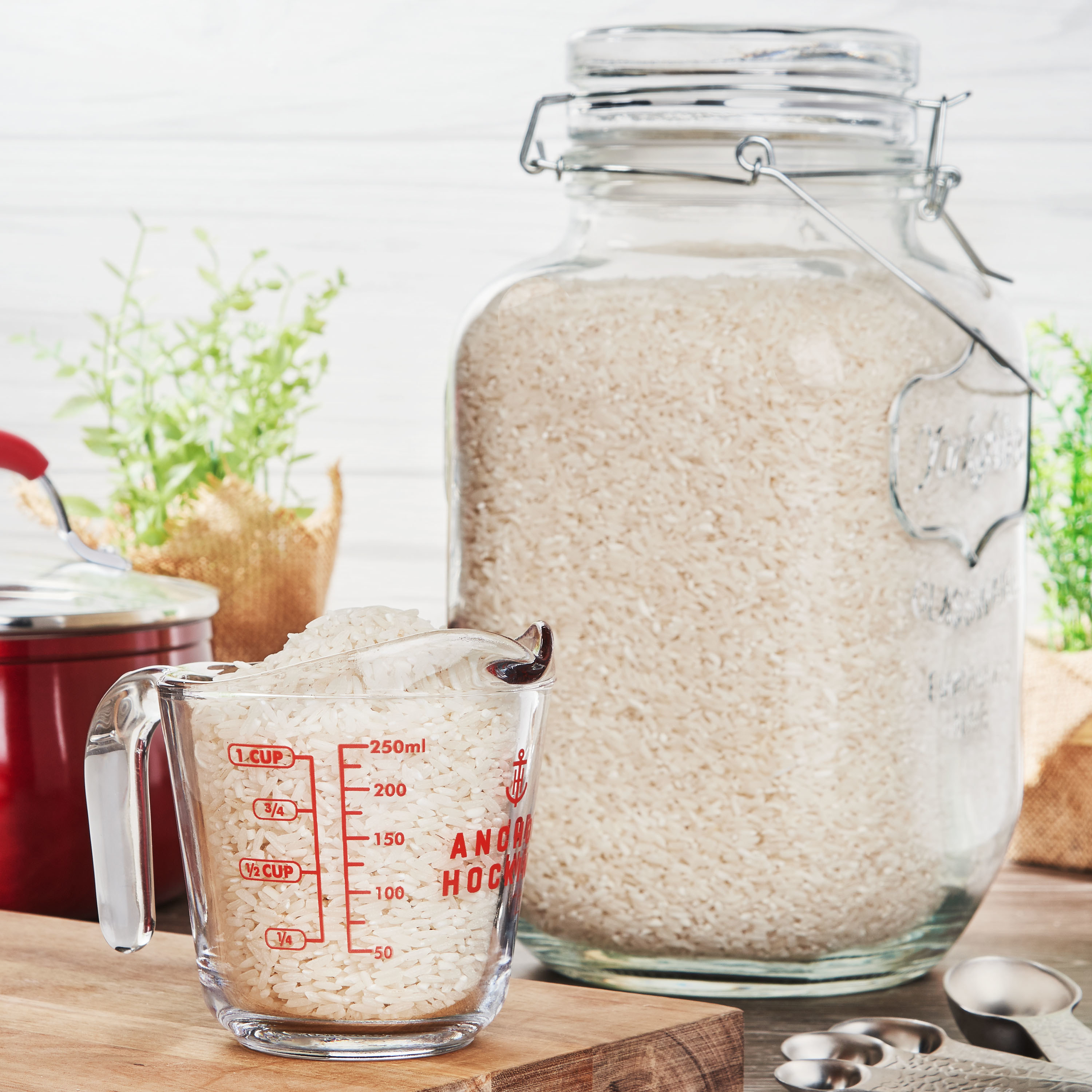 a cup and canister of rice on a counter