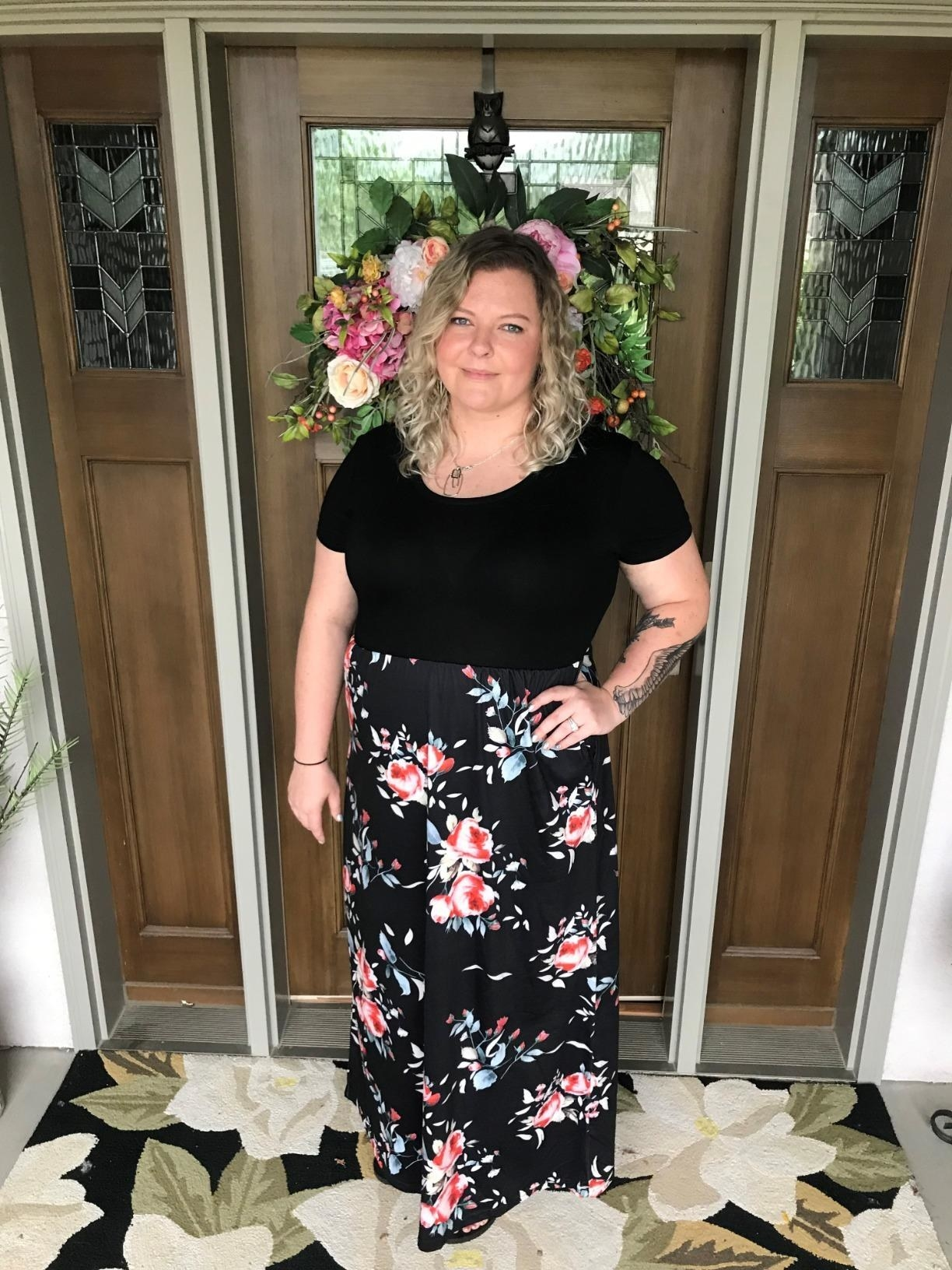 Reviewer wearing black dress with light red floral pattern, stops past the ankle