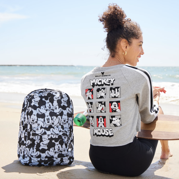 model wearing grey cropped hoodie with illustrations of mickey mouse all over the back