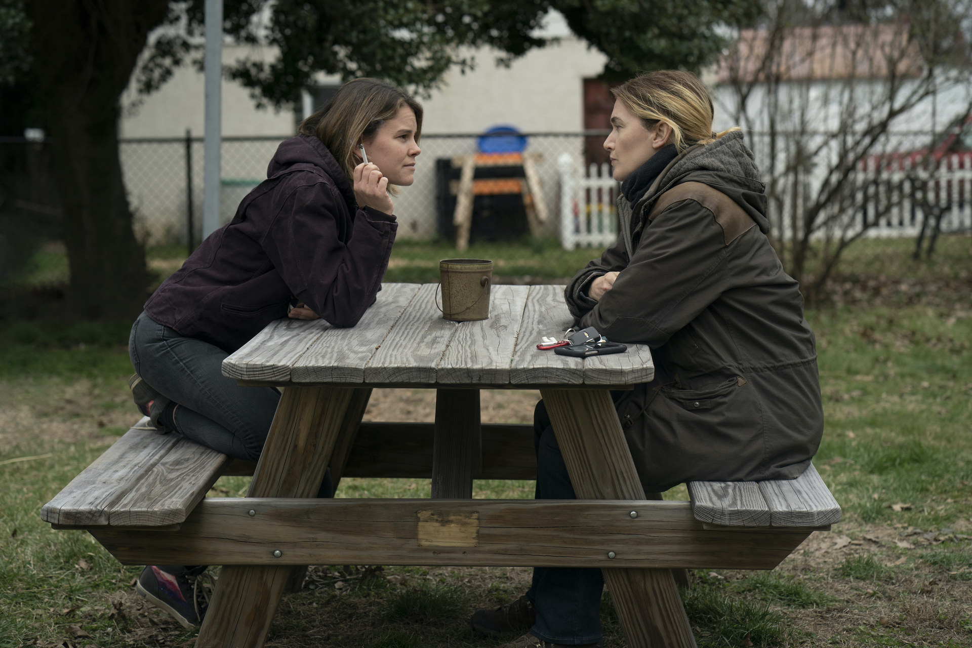 """Sosie Bacon leaning across a table talking to Kate Winslet in """"Mare of Easttown"""""""