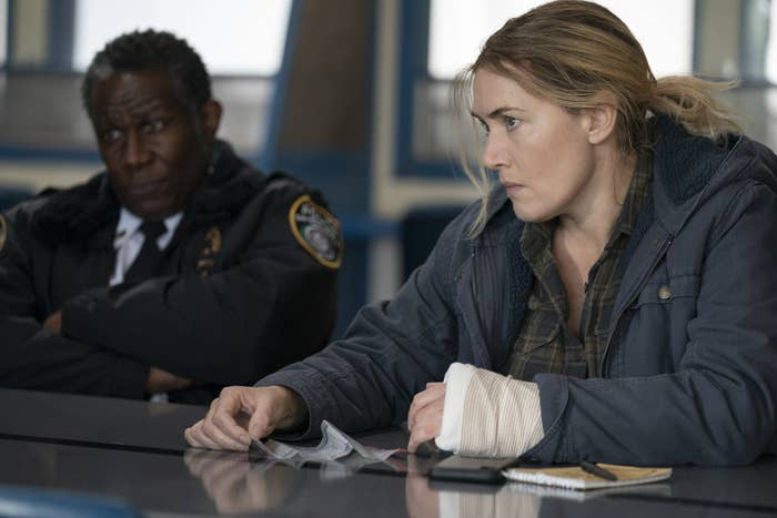 """Kate Winslet sitting at a table with John Douglas Thompson as police Chief Carter in """"Mare of Easttown"""""""