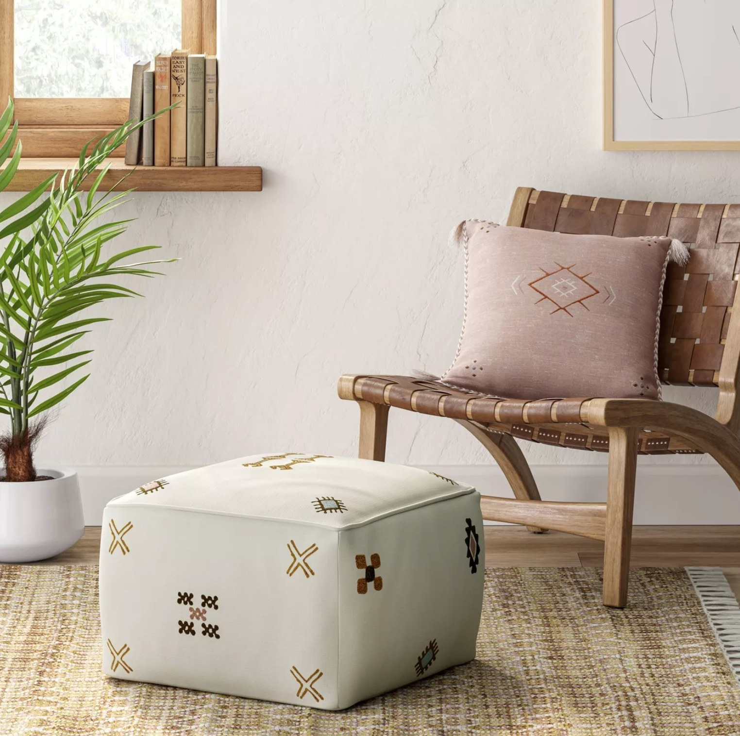 the cream pouf with brown designs in front of a chair with a pink pillow