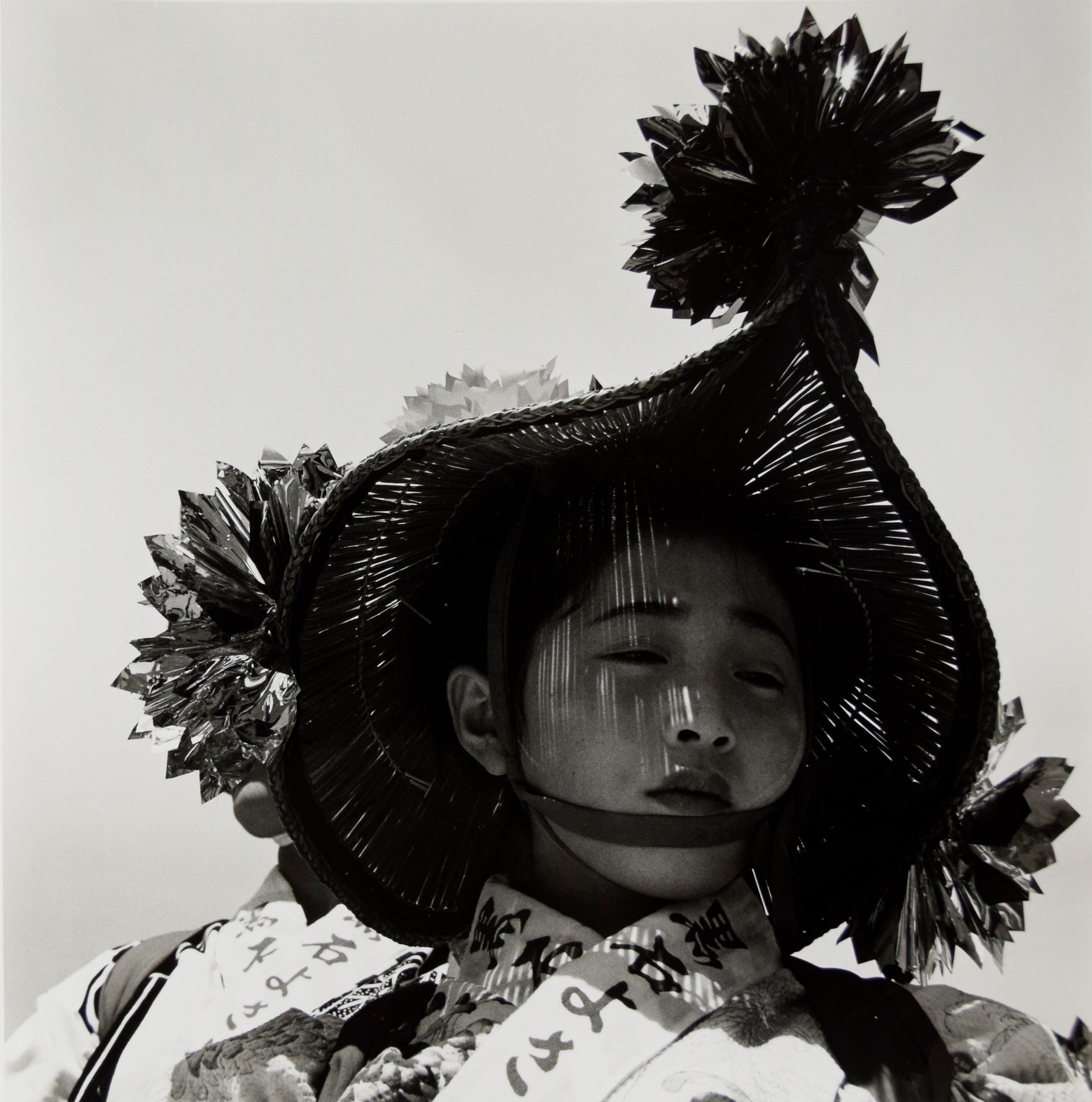 A young girl in traditional regional Japanese clothing, with a shadow on her face from her hat