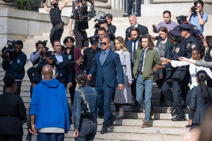 Elliot Stabler and his family walking down the courthouse steps surrounded by media and police officers