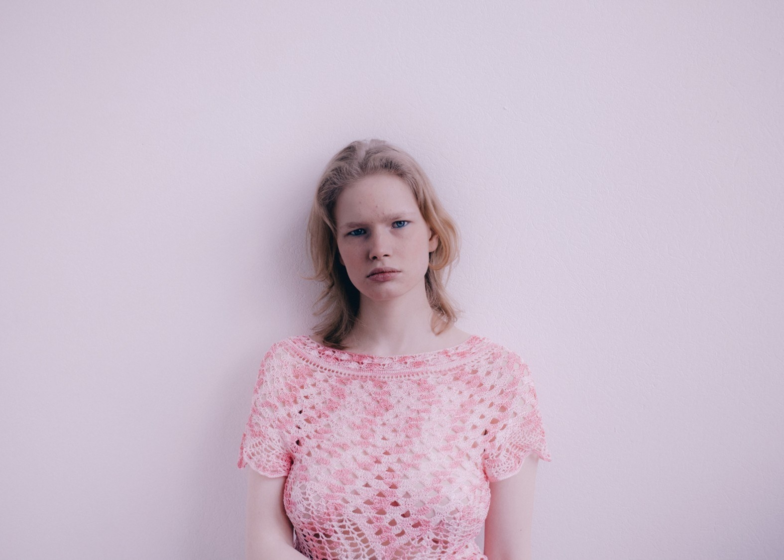 A young girl in a pink knit top against a plain wall, looking at the camera