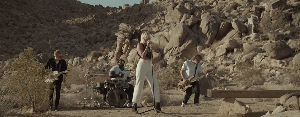 A full band plays in the desert in front of a rock formation with Hanna behind the microphone