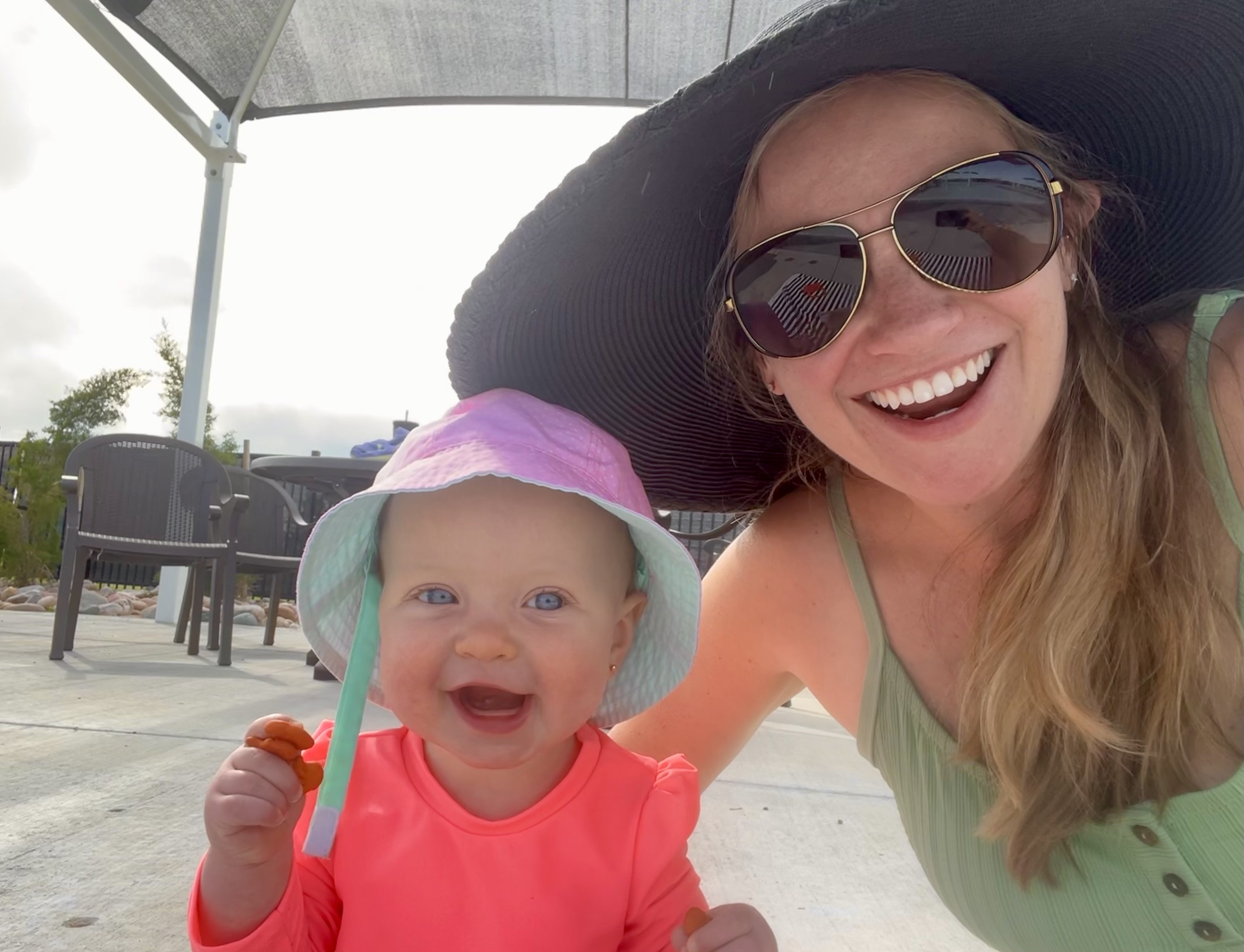The author and her youngest kid, smiling at the town pool