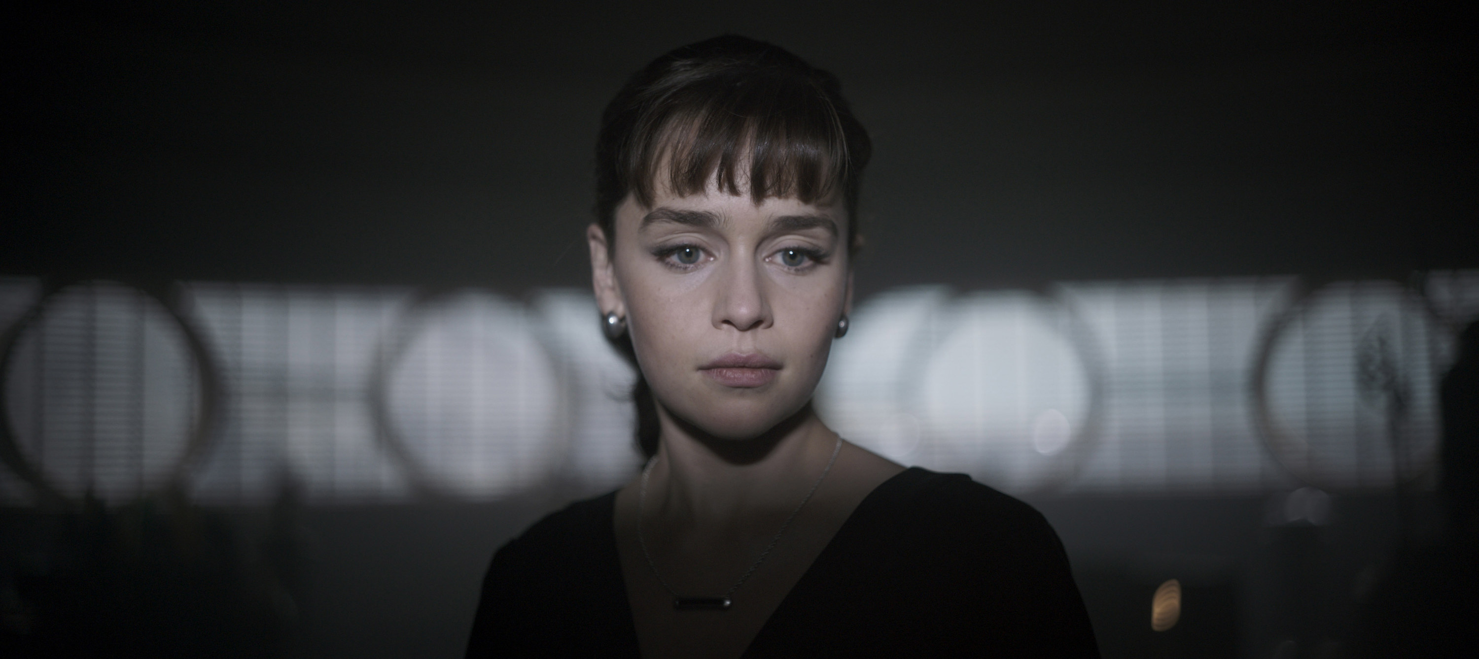 """Emilia Clarke as Qi'ra, looking thoughtful, faces the camera but looks off to the left in """"Solo: A Star Wars Story"""""""