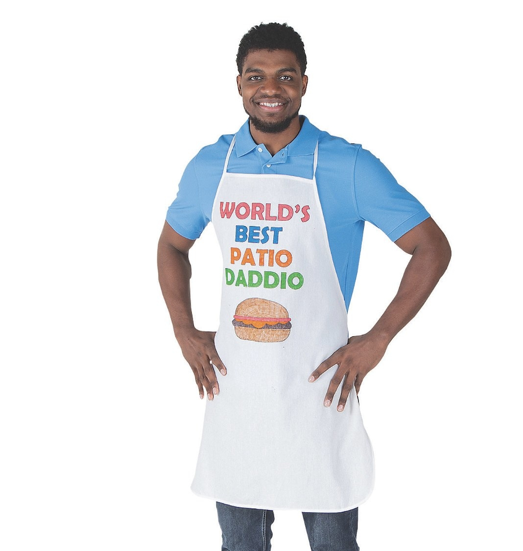 """There is an adult wearing a white apron that says """"WORLD'S BEST PATIO DADDIO"""" with a hamburger underneath"""
