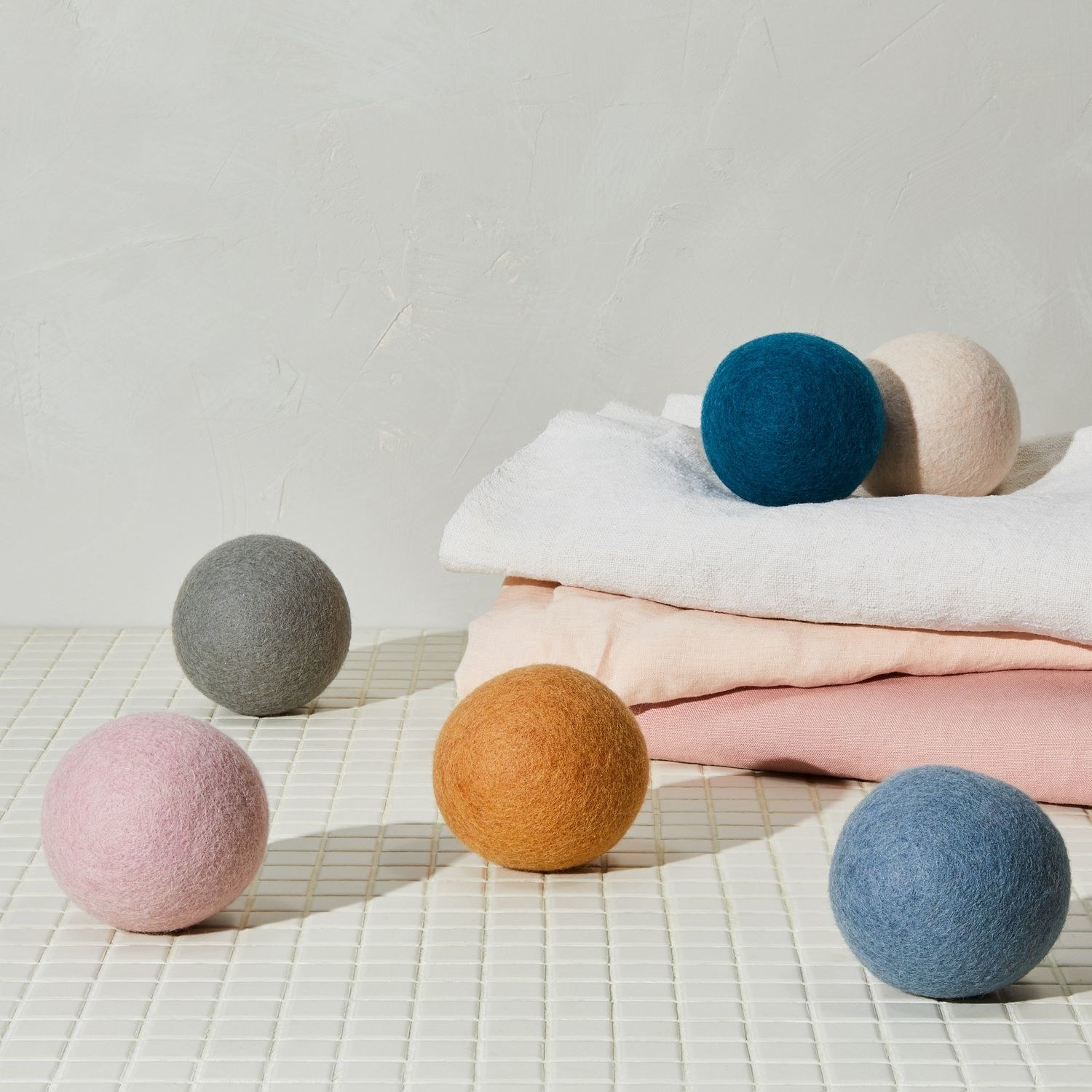 colorful dryer balls on top of folded linens