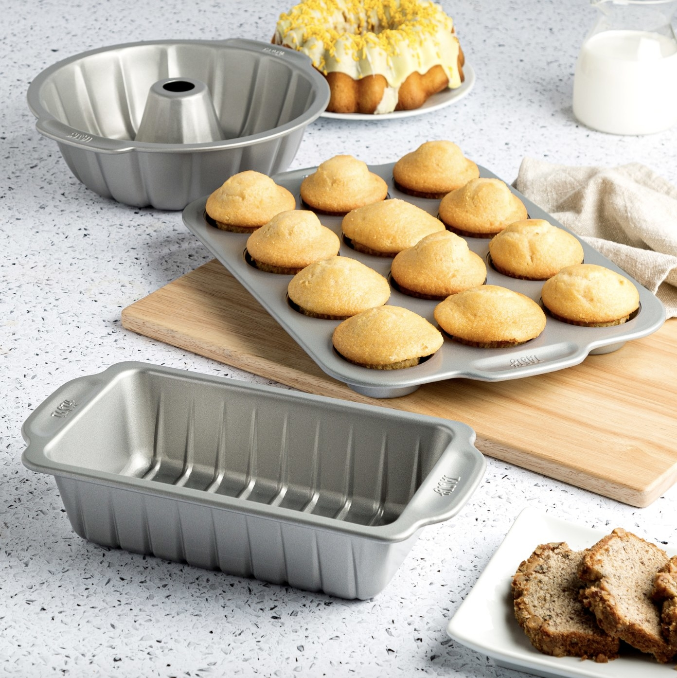 The set is stainless still and is surrounded by/holding muffins, cake, milk and bread