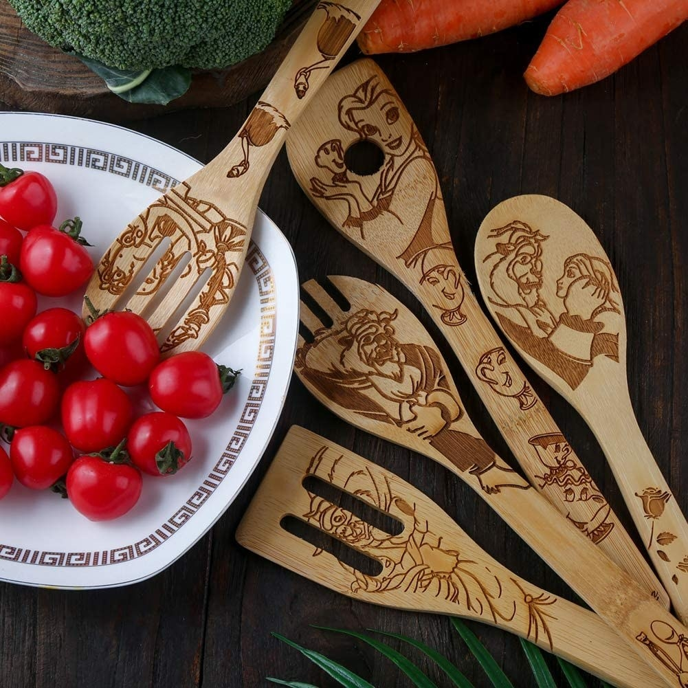 Beauty and the Beast-inspired bamboo cooking utensils next to plate of tomatoes
