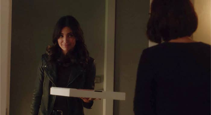 Maggie Sawyer stands in Alex Danvers' doorway in a leather jacket holding a pizza box.