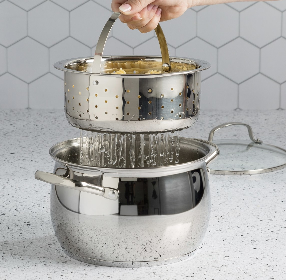 There is large stainless steal pot underneath a smaller one with holes draining pasta