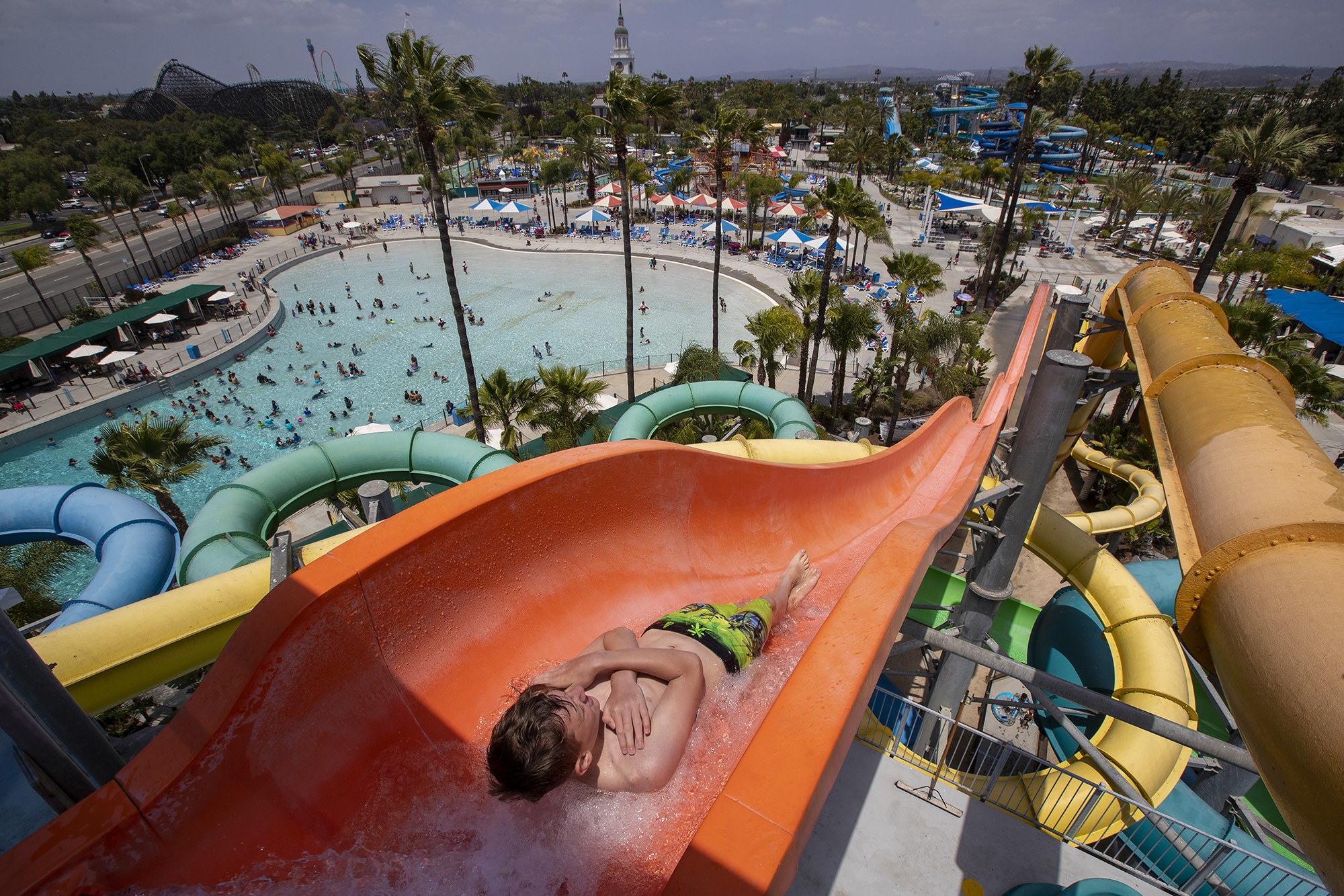 Overhead view of a boy going down a waterslide, with people in a water park behind him