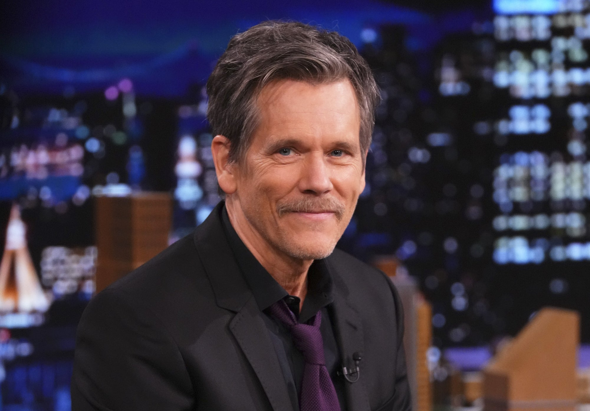 Photo of Kevin Bacon smiling on a talk show