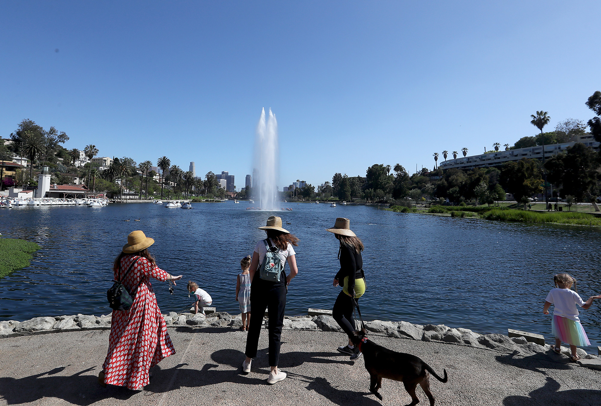 Three women in hats in front of a human-made fountain and a lake