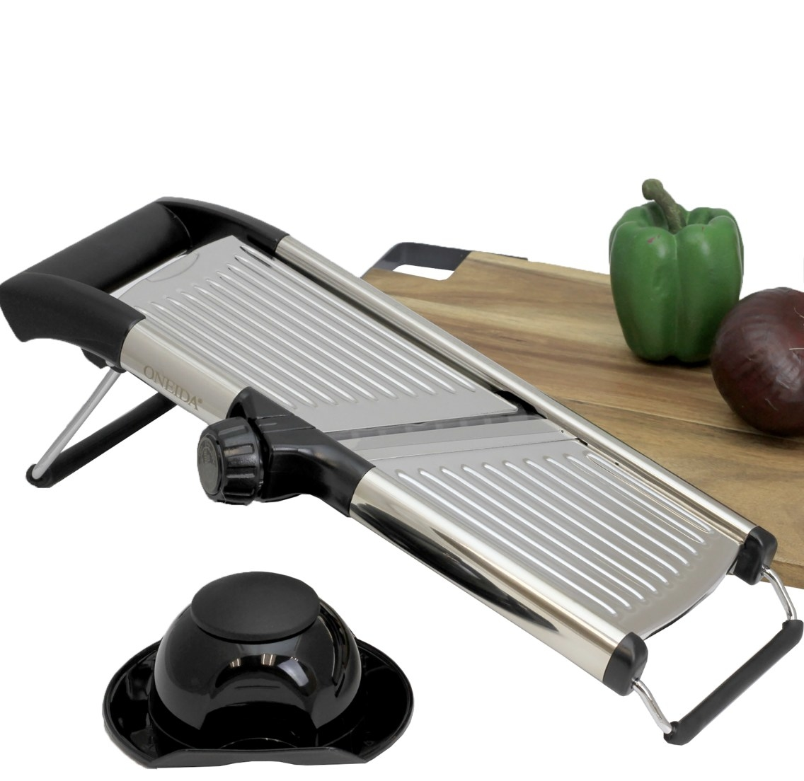 The silver and black device is next to a tan cutting board holding veggies