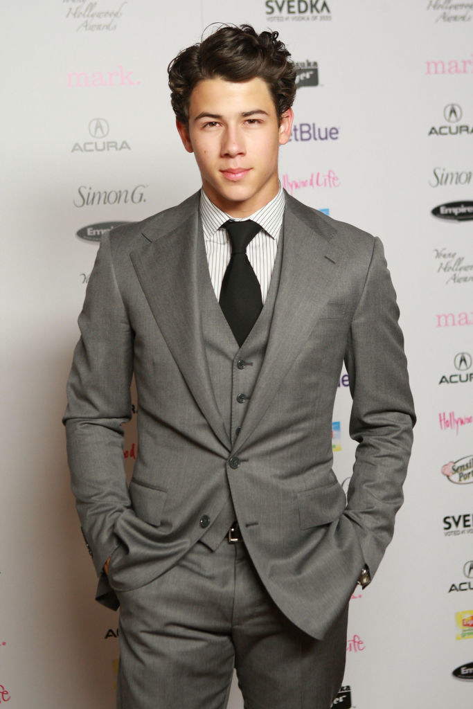 wearing a suit and giving a smoldering look to the camera
