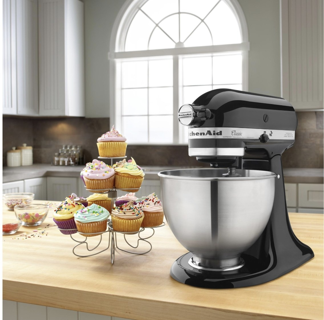 """The device has black base says """"KitchenAid"""" and a silver mixing bowl, and it's surrounded by cupcakes"""