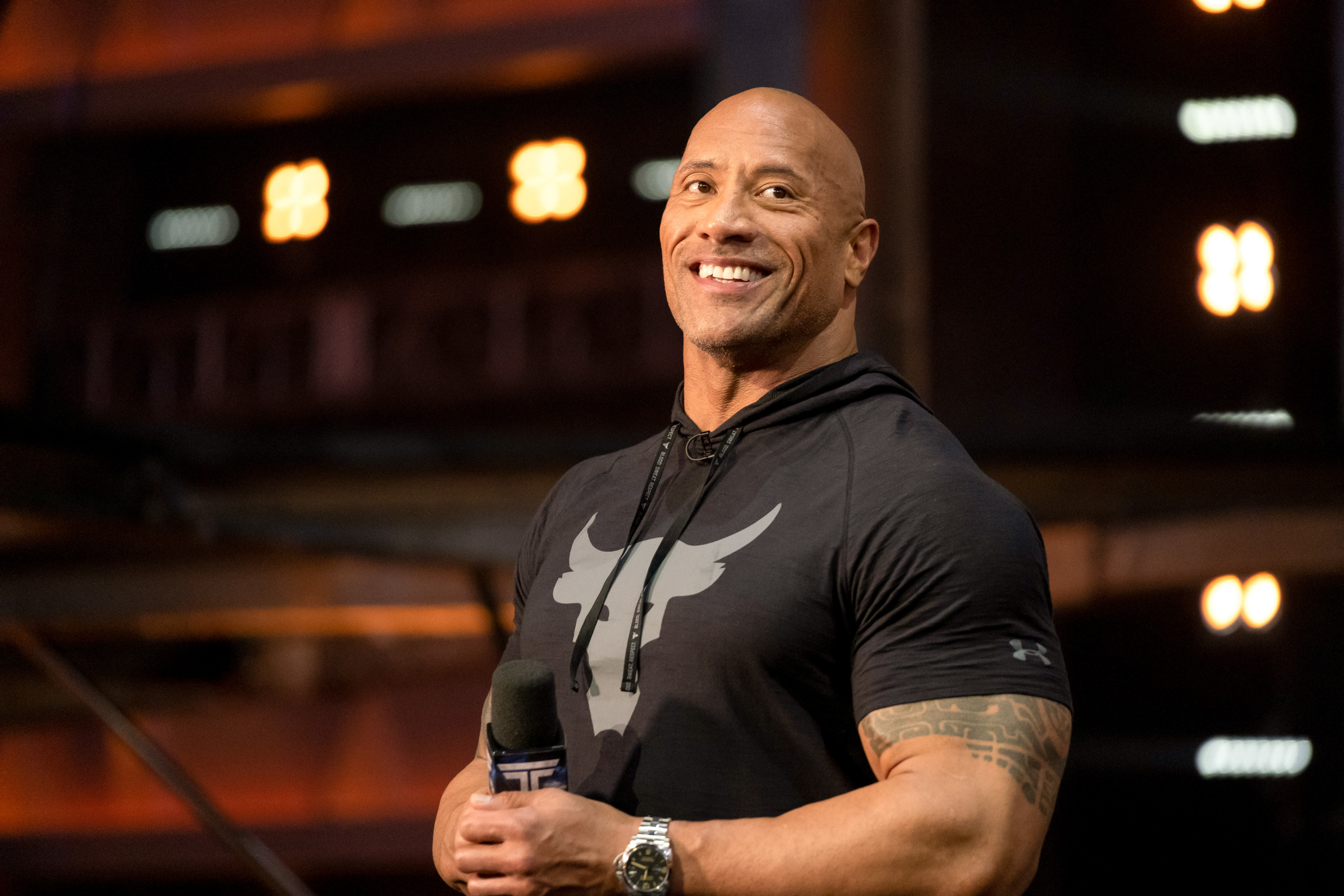 """Photo of Dwayne """"The Rock"""" Johnson smiling onstage"""