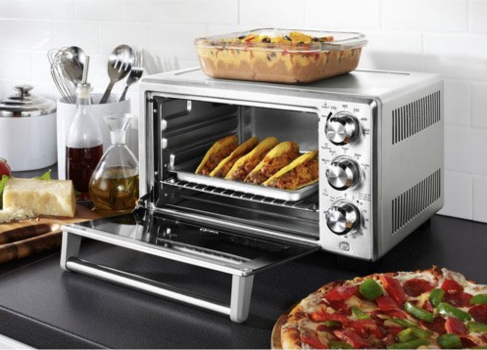The silver toaster oven has various foods inside and surrounding it