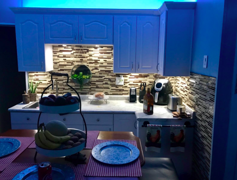 A customer review photo of their cabinets with lighting above and below