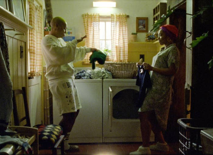 Denise in shorts and a sweatshirt with Alicia in a hair wrap and casual dress, dancing while folding their laundry in front of the dryer in their laundry room