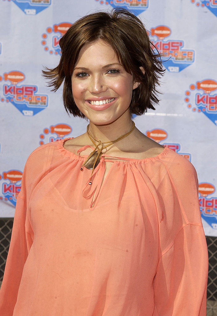 with a pixie cut and a light orange blouse