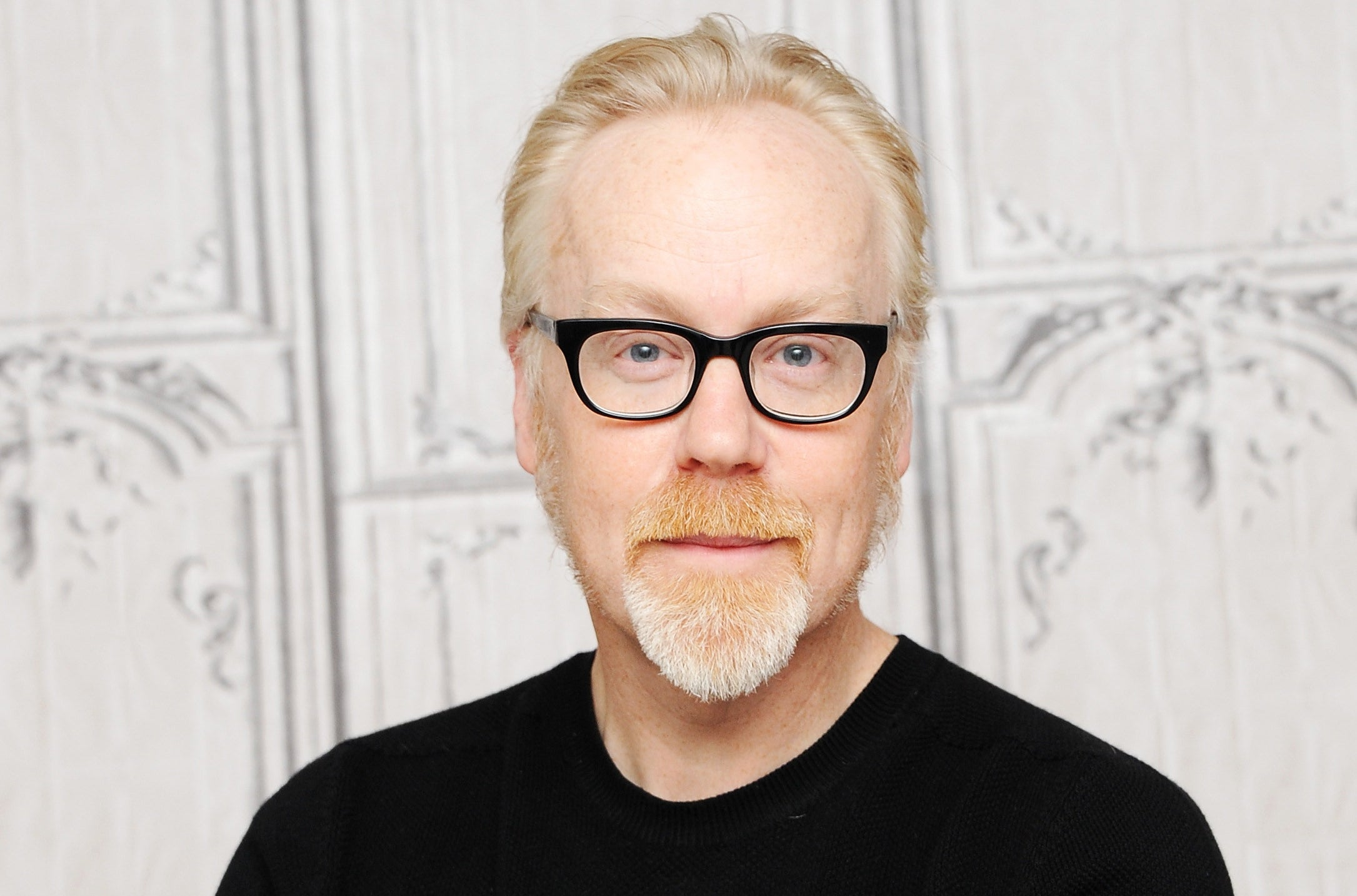 Headshot-style photo of Adam Savage in a black shirt and glasses