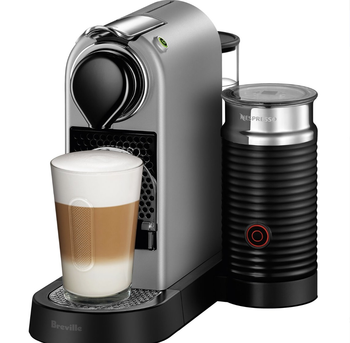 """The black and silver machine says """"NESPRESSO"""" and """"Breville"""" with a brewed coffee with foam in a cup"""