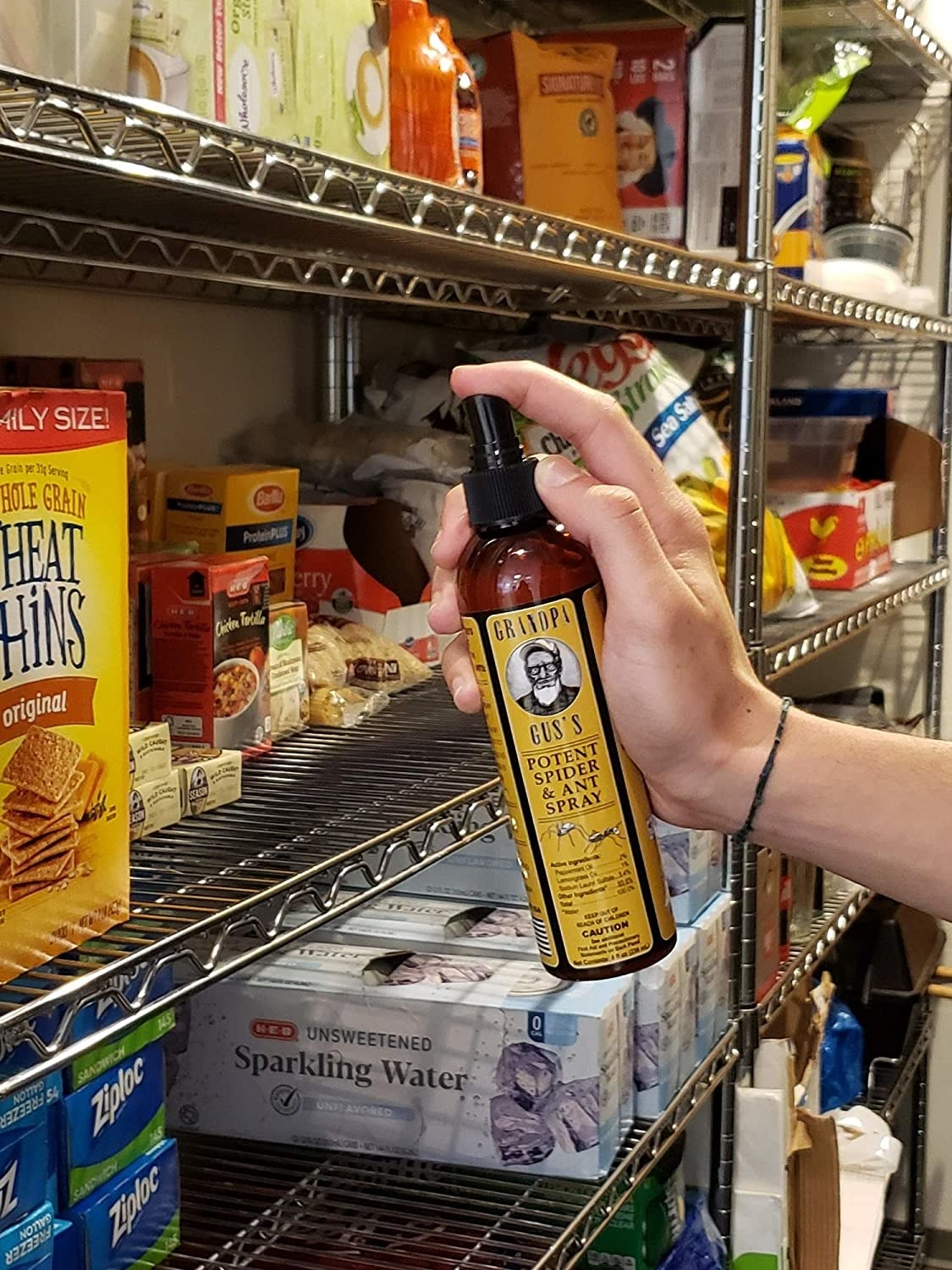 Person spraying shelves of packaged food in a grocery store