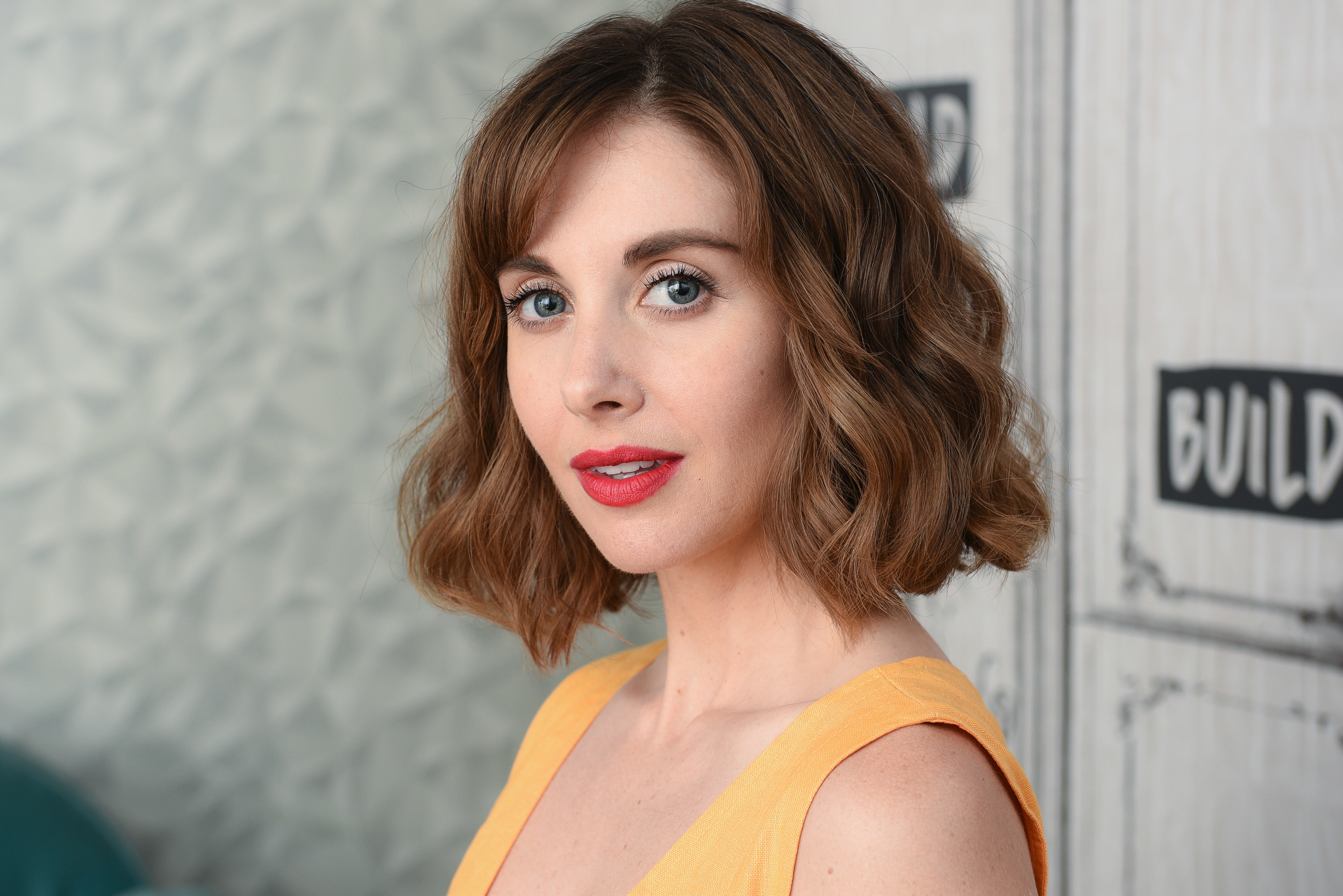 Headshot style photo of Alison Brie in yellow dress
