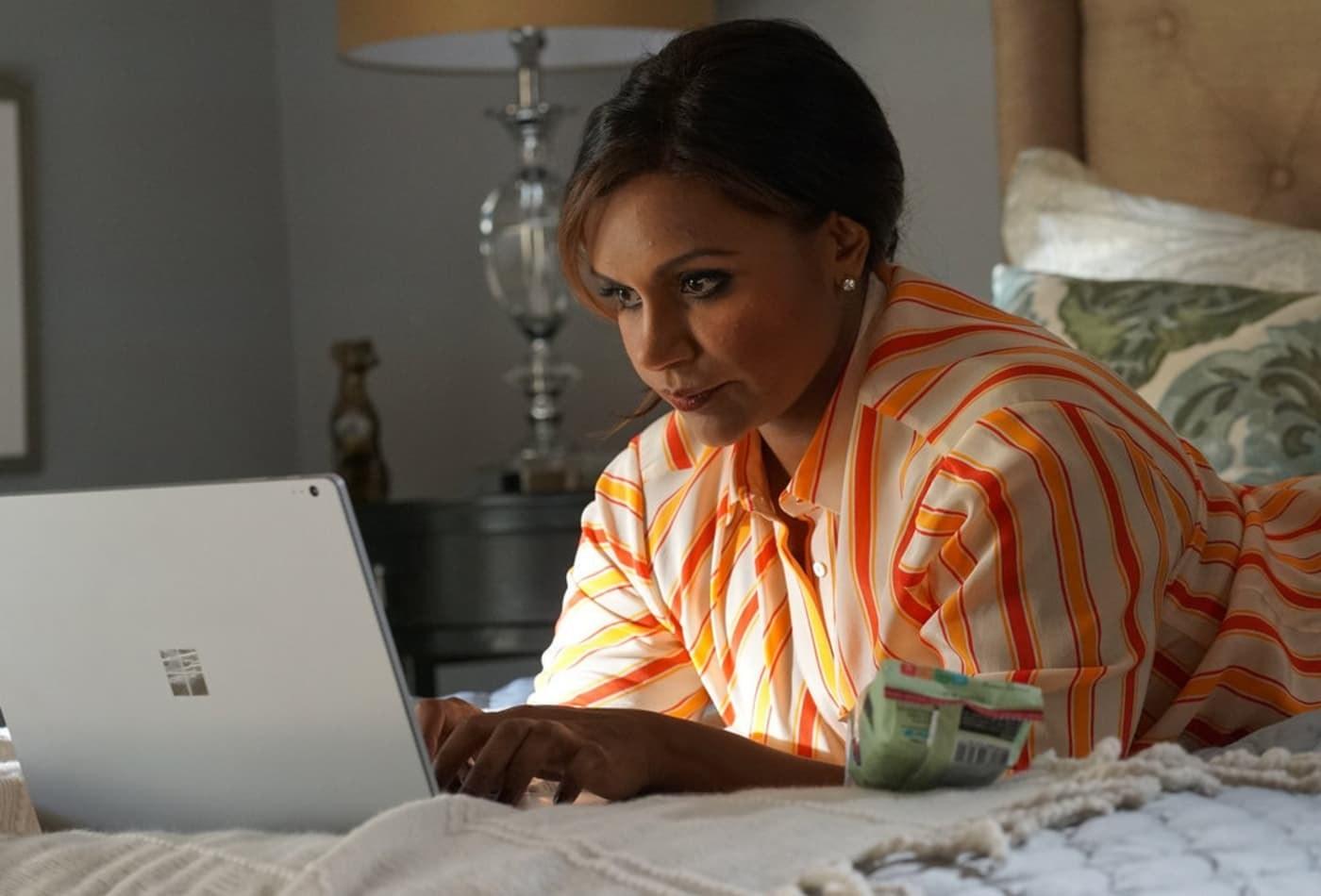 mindy kaling types on a laptop